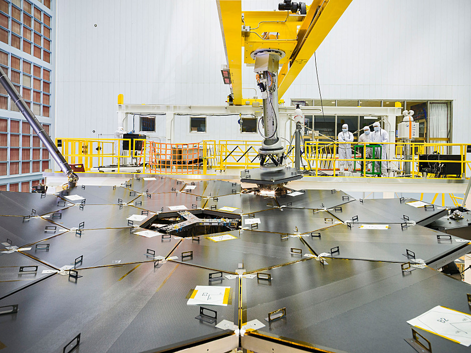 Inside a massive clean room at NASA's Goddard Space Flight Center in Greenbelt, Maryland the James Webb Space Telescope team used a robotic am to install the last of the telescope's 18 mirrors onto the telescope structure. Each mirror segment is protected by a black cover while work on the instrument continues. Image credits: NASA/Chris Gunn.