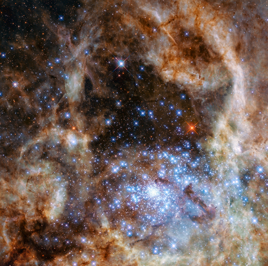 This image shows the central region of the Tarantula Nebula in the Large Magellanic Cloud. The young and dense star cluster R136 can be seen at the lower right of the image. This cluster contains hundreds of young blue stars, among them the most massive star detected in the Universe so far. Using the NASA/ESA Hubble Space Telescope astronomers were able to study the central and most dense region of this cluster in detail. Here they found nine stars with more than 100 solar masses. Click the image for a full-size version. Image credit: NASA, ESA, P. Crowther (University of Sheffield).