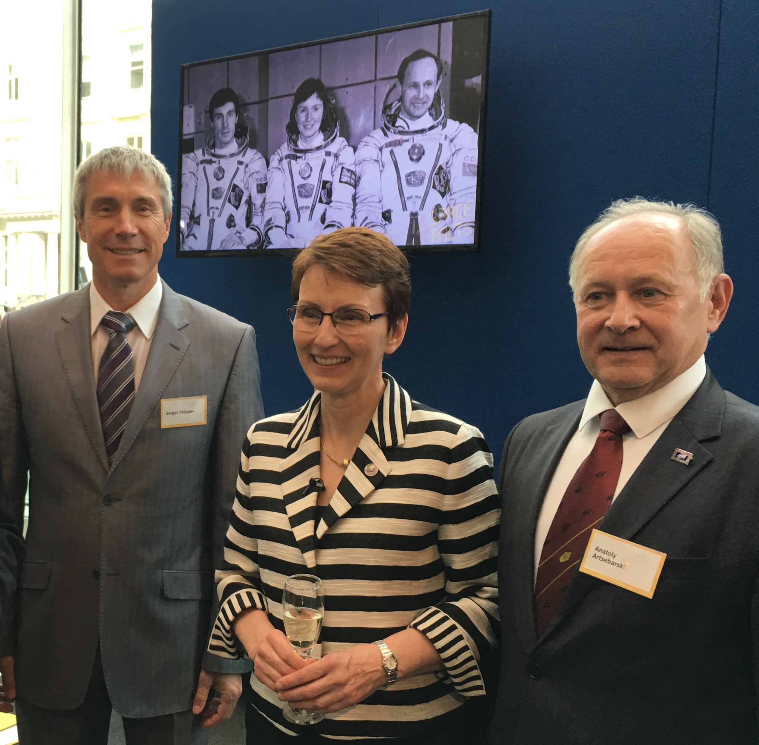 The Soyuz TM-12 crew then and now. (Left to right) Sergei Krikalev, Helen Sharman and Anatoly Artsebarski with their crew photo from 1991 appearing on the screen behind.