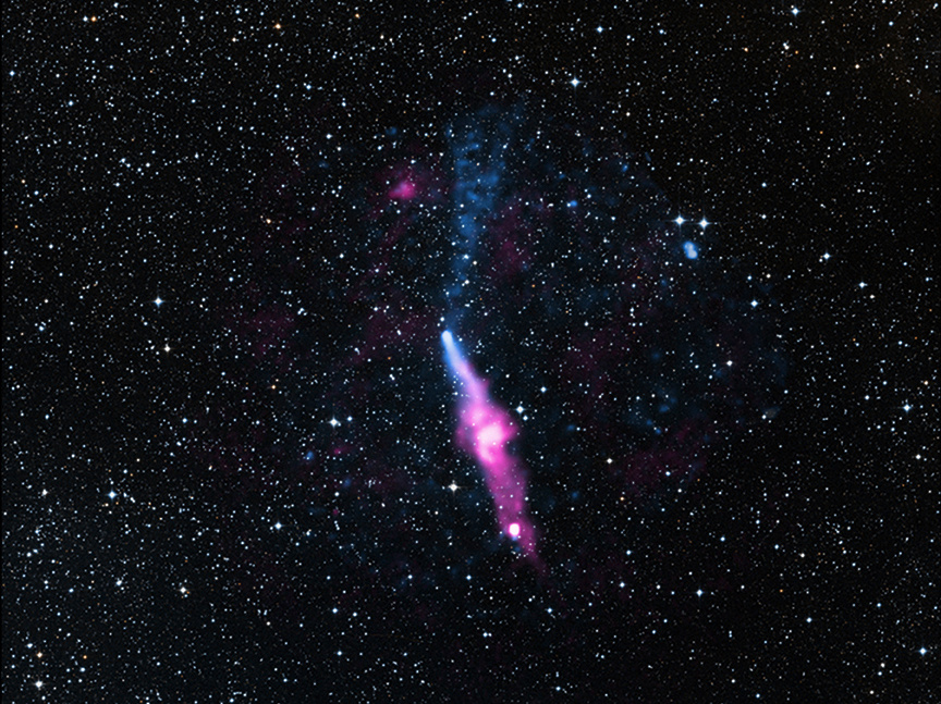 Pulsars were first discovered in 1967 and today astronomers know of over a thousand such objects. The pulsar PSR J1509-5850, appearing as the bright white spot in the centre of this picture, has generated a long tail of X-ray emission trailing behind it, as seen in the lower part of the image. This pulsar has also generated an outflow of particles in approximately the opposite direction. PSR J1509-5850 lies about 12,400 light-years from Earth in the constellation of Circinus. In this image, X-rays detected by Chandra (blue) and radio emission (pink) have been overlaid on a visible light image from the Digitised Sky Survey of the field of view. Image credit: X-ray: NASA/CXC/George Washington Univ./N.Klingler et al; Optical: DSS; Radio: CSIRO/ATNF/ATCA.